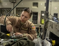 Staff Sgt. Alicia Clark attaches an oxygen line before an aeromedical evacuation aboard a C-17 Globemaster III at the 379th Air Expeditionary Wing in Southwest Asia, Dec. 9, 2013. Clark, a 379th Exped